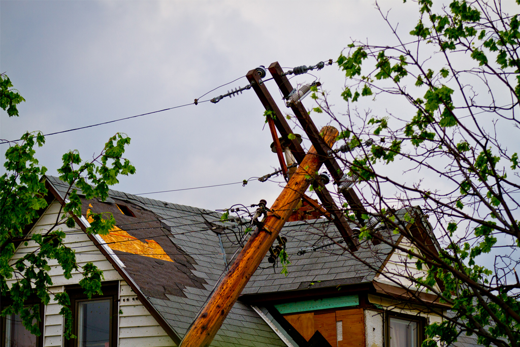 fallen electrical pole against house